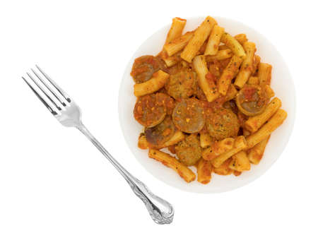 marinara sauce: A serving of rigatoni pasta with sausage and meatballs in a marinara sauce on a plate with a fork to the side isolated on a white background.