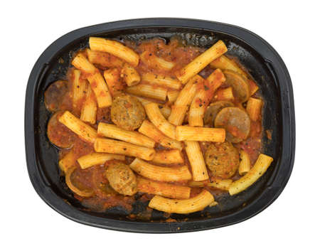 A TV dinner of rigatoni pasta with sausage and meatballs in a marinara sauce in a black tray isolated on a white background.