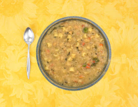 A serving of white bean soup in a bowl with a spoon to the side atop a yellow floral tablecloth.