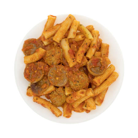 marinara sauce: Top view of a serving of rigatoni pasta with sausage and meatballs in a marinara sauce on a plate isolated on a white background.