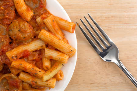 marinara sauce: Top close view of a serving of rigatoni pasta with sausage and meatballs in a marinara sauce on a plate with a fork to the side atop a wood table.