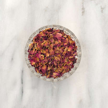 countertop: Top view of a glass bowl of dried red rosebuds and petals that have been crushed atop a gray marble countertop.