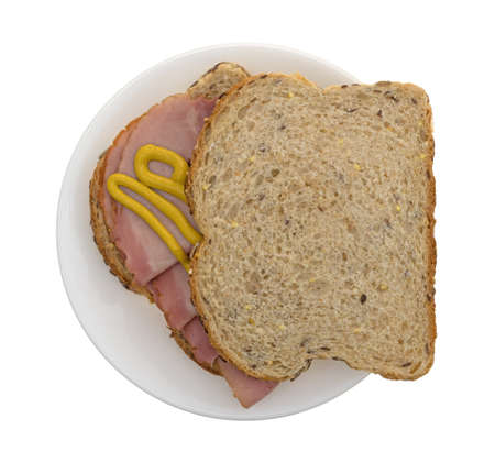 Top view of an applewood smoked ham sandwich with mustard on wheat bread atop a plate isolated on a white background.