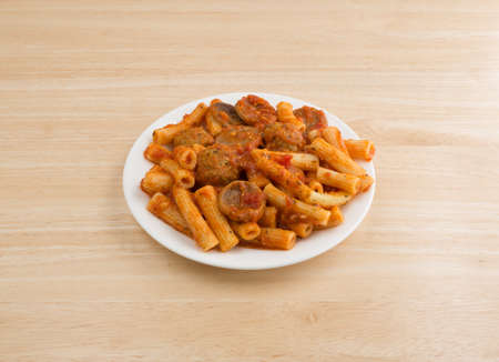 marinara sauce: A serving of rigatoni pasta with sausage and meatballs in a marinara sauce on a plate atop a wood table.