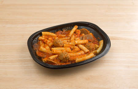 marinara sauce: TV dinner of rigatoni pasta with sausage and meatballs in a marinara sauce on a wood table.