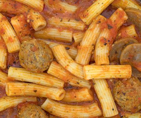 marinara sauce: A very close view of rigatoni pasta with sausage and meatballs in a marinara sauce.