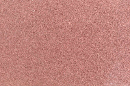 A very close view of maroon sandpaper.