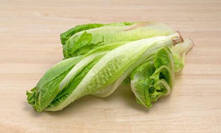 romaine lettuce: Heads of romaine lettuce on a wood cutting board.