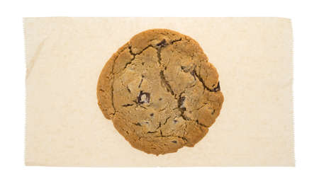 throwaway: A double chocolate chip cookie atop a brown paper tissue isolated on a white background. Stock Photo