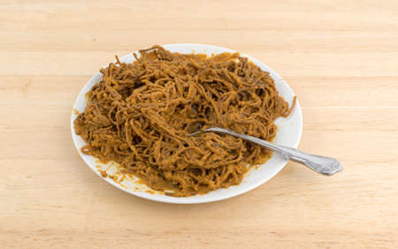 A serving of soybean spaghetti with tomato sauce on a plate with a spoon inserted into the food atop a wood table.