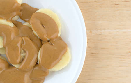 Top close view of sliced bananas covered with creamy peanut butter on a white plate atop a wood table. Stock Photo