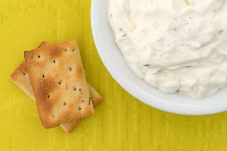 Top close view of rosemary and olive oil seasoned crackers next to a bowl of French onion dip on a bright yellow tablecloth.