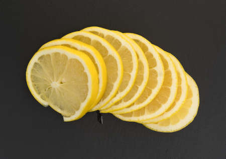 Top view of several white grapefruit slices on a black slate cutting board. Stock Photo