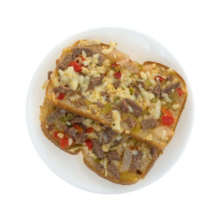 Top view of two pieces of a steak with cheese and vegetables sandwich on a plate isolated on a white background. Stock Photo