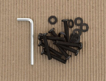 hex key: Several bolts and washers and hex key for do it yourself furniture assembly atop a piece of cardboard.