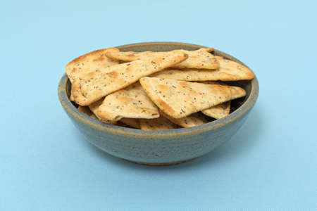 pizza crust: Pizza crust chips in an old stoneware bowl atop a blue fabric tablecloth.