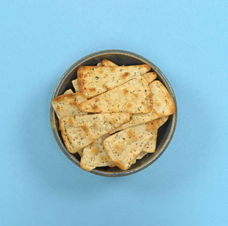 pizza crust: Top view of pizza crust chips in an old stoneware bowl atop a blue fabric tablecloth.
