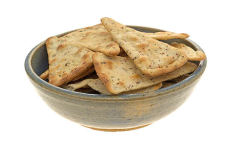 pizza crust: Seasoned pizza crust chips in an old stoneware bowl isolated on a white background.