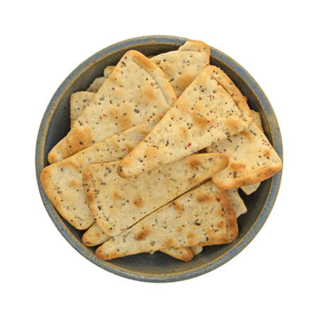 pizza crust: Top view of seasoned pizza crust chips in an old stoneware bowl isolated on a white background.