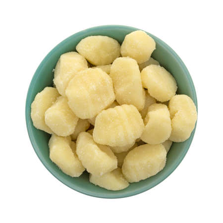Top view of plain potato gnocchi in a green bowl isolated on a white background.