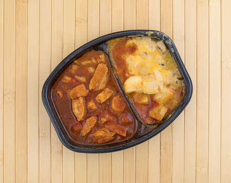 Top view of a TV dinner with chunks of chicken in a thick barbecue sauce plus cheese covered potatoes on a wood place mat. 版權商用圖片