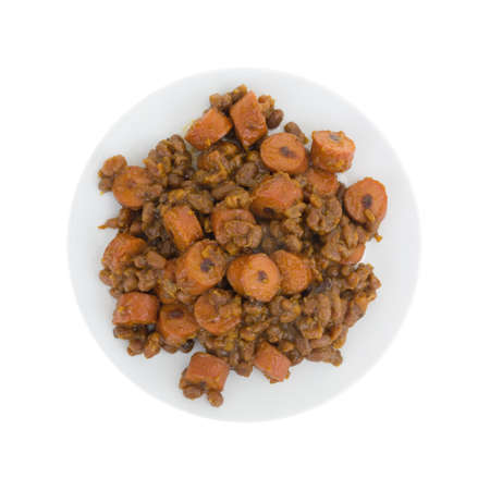 molasses: Top view of baked beans and sliced hot dogs on a plate isolated on a white background.