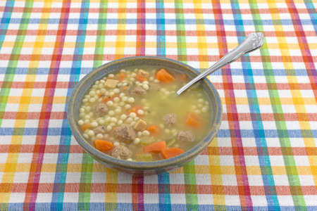 Bowl of Italian style wedding soup with a spoon in the food atop a colorful cloth place mat.