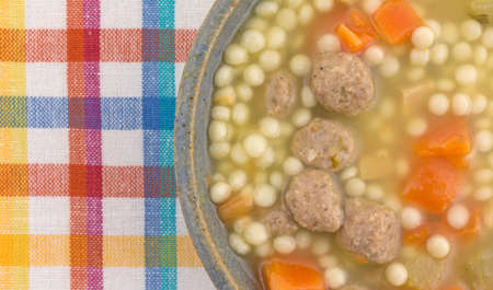Top close view of a stoneware bowl filled with Italian style wedding soup atop a colorful cloth place mat.