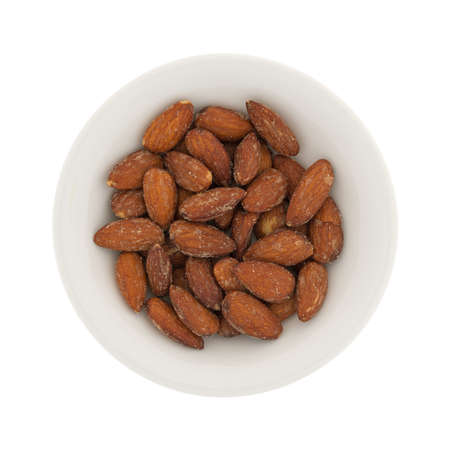 Top view of hickory smoked almonds in a small bowl isolated on a white background.