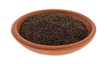 小さな粘土ボウルは、白い背景に分離された緩い葉黒茶でいっぱい。 写真素材