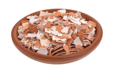 Small bowl filled with crushed egg shells isolated on a white background.