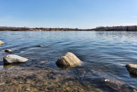 View of shoreline boulders and sea grass at high tide at Stockton Springs Maine in the late winter.
