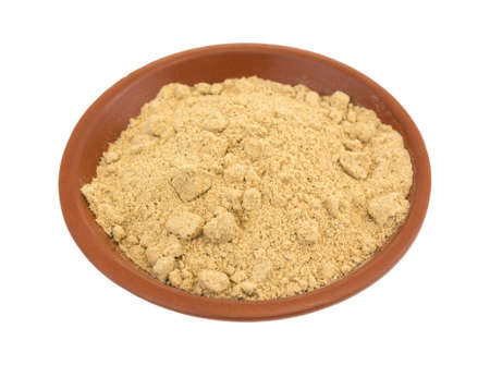 Seasoning mixture for beef stew in a small clay bowl isolated on a white background.
