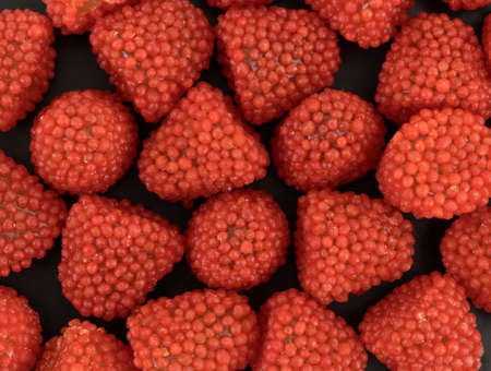 A very close view of raspberry shaped candies on a black background.