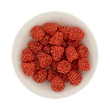 Vista superior de un pequeño cuenco lleno de caramelos en forma de frambuesa aislado en un fondo blanco.