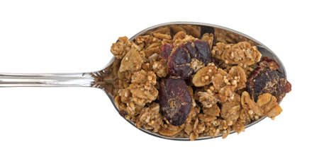 Top view of organic cranberry and nut dry granola cereal on a spoon against a white background.
