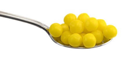 Side view of a spoon filled with lemon candy on a white background.