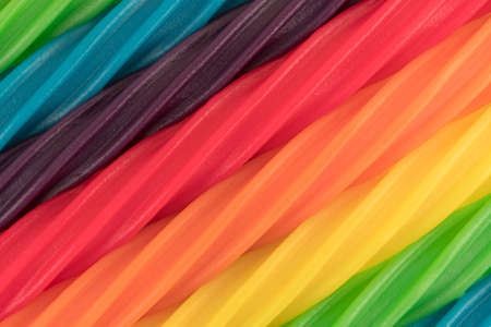 A very close view of colorful spiral licorice sticks in rows at an angle.