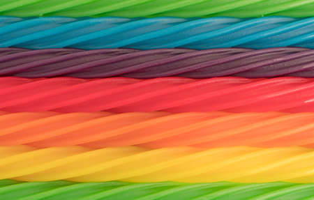 A very close view of colorful spiral licorice sticks in rows.