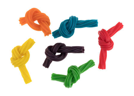Top view of a group of colorful spiral licorice sticks that have been tied in small knots isolated on a white background. Stock Photo