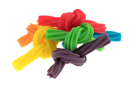A group of colorful spiral licorice sticks that have been tied in small knots isolated on a white background.