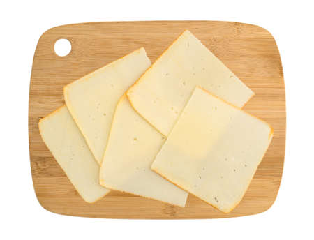 Top view of muenster cheese slices on a wood cutting board isolated on a white background.