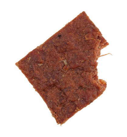 Top view of a piece of peppered beef jerky with one bite taken isolated on a white background.