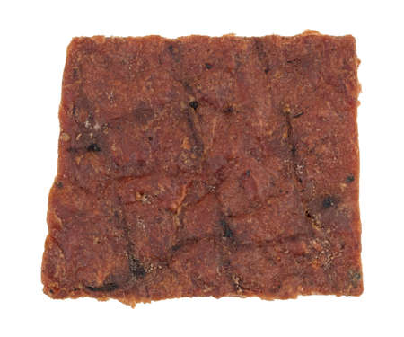 Top view of a piece of peppered beef jerky isolated on a white background.