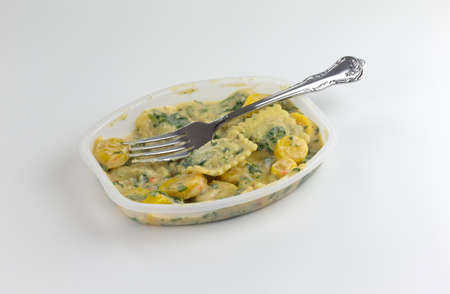 A spinach ravioli TV dinner with vegetables in a microwavable tray with a fork on the food atop a white table top. Stock Photo