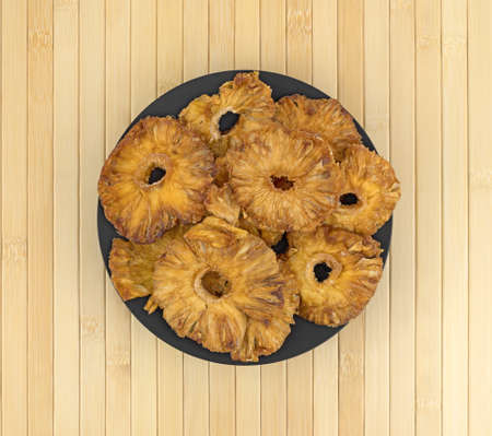 Top view of a black bowl filled with sun dried pineapple slices atop a wood place mat.