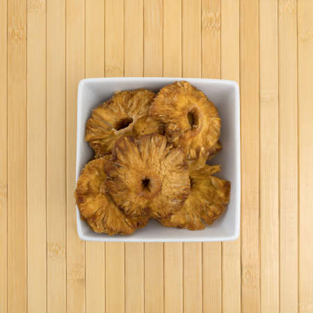 Top view of a square bowl filled with sun dried pineapple slices on a wood place mat.