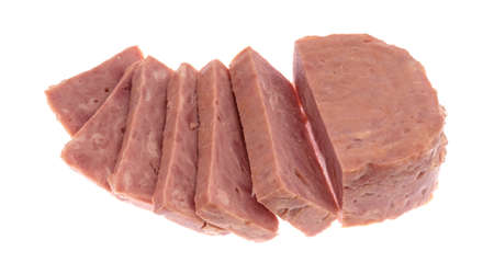 Several thick slices of a whole canned ham isolated on a white background.