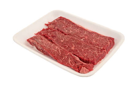 Raw beef loin sirloin grilling tips on a foam butcher tray isolated on a white background. Stock Photo