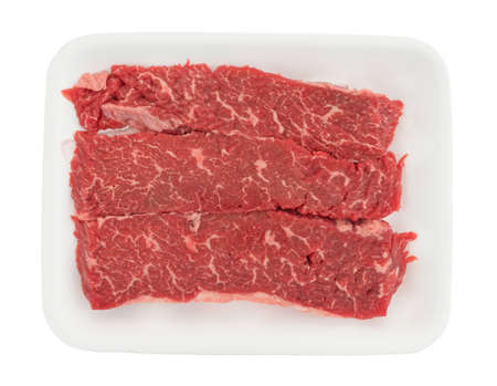 Top view of raw beef loin sirloin grilling tips on a foam butcher tray isolated on a white background. Stock Photo